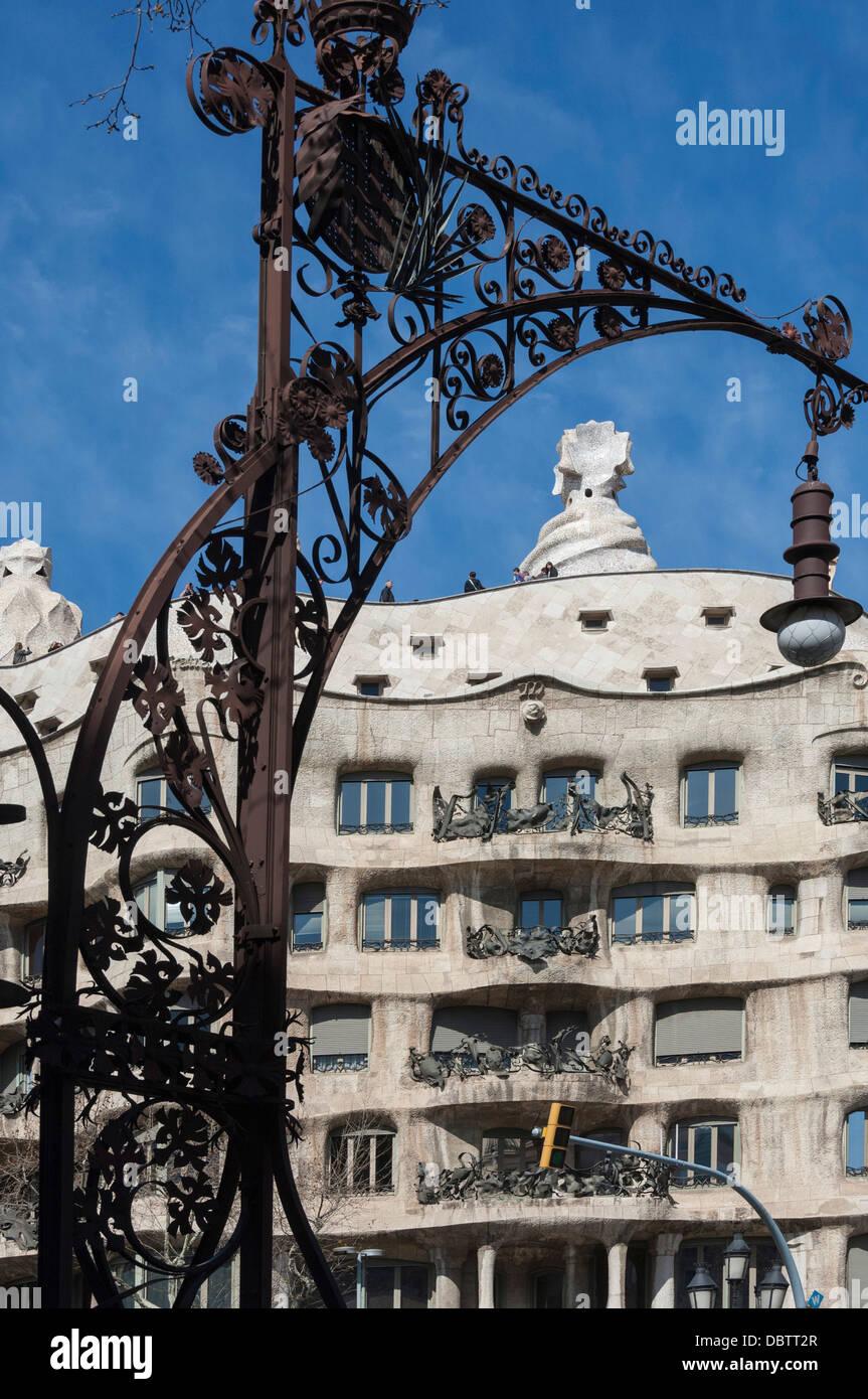 A wrought iron lamp frames La Pedrera (Casa Mila), Passeig de Gracia, Barcelona, Catalunya, Spain - Stock Image