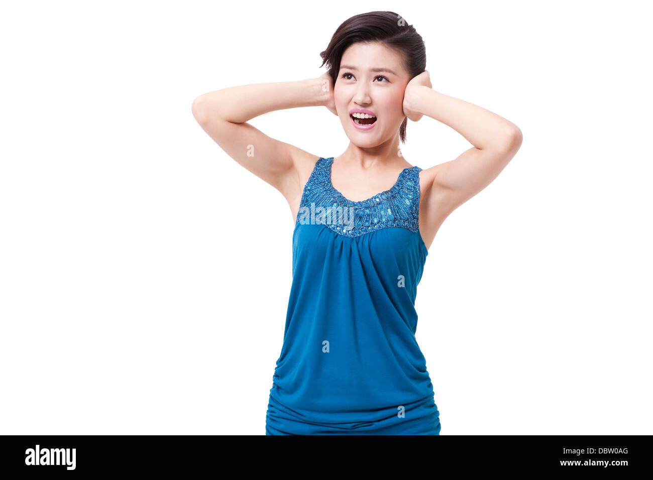 Young woman with hands covering ears - Stock Image