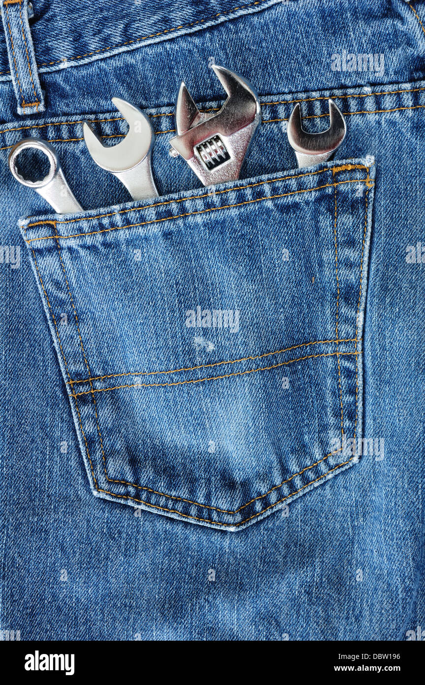 DIY / workman's hand tools in the back pocket of a pair of denim jeans - Stock Image