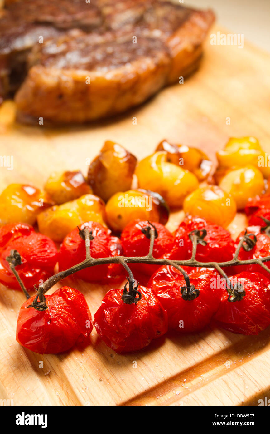 Roasted red and yellow tomatoes with a rib of beef on a wooden chopping board. - Stock Image
