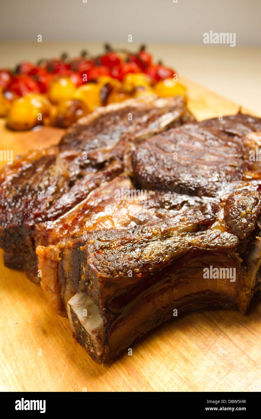 Roast rib of beef on a wooden chopping board, with roasted red and yellow tomatoes - Stock Image