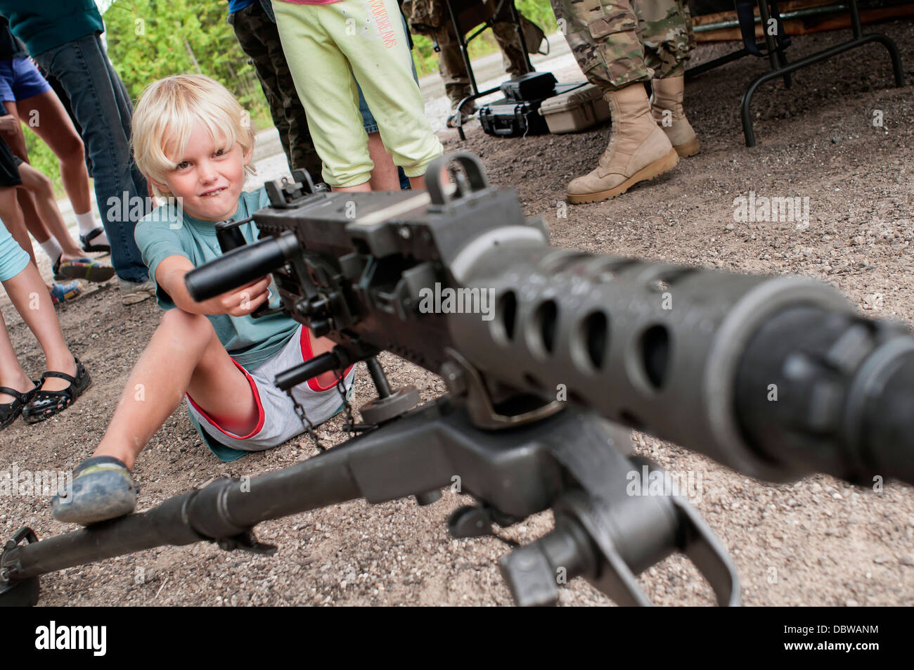 A young boy sits behind a heavy machine gun during a static display at the Nautical Festival August 2, 2013 in Rogers - Stock Image