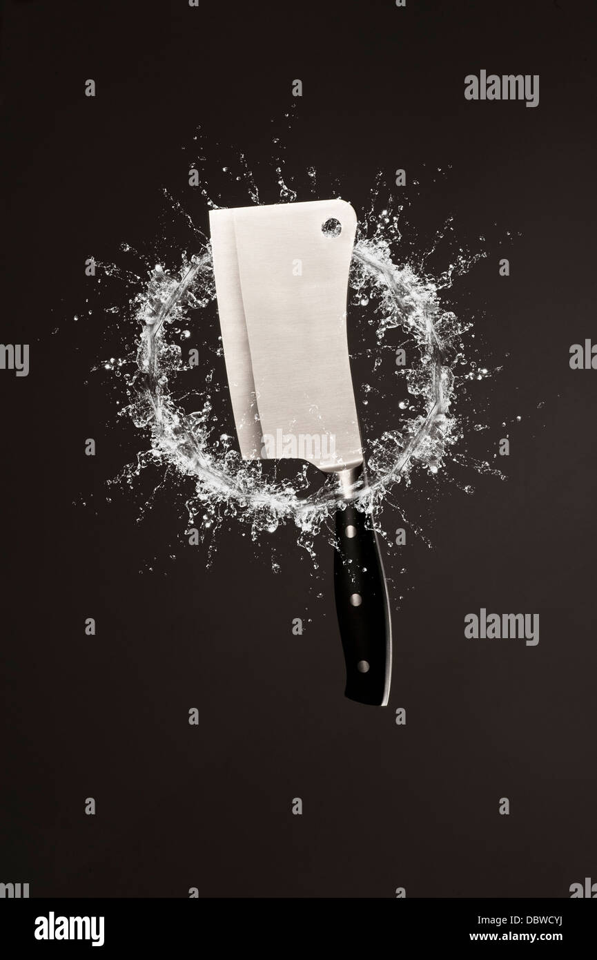 Metal cleaver suspended in air with splashing ring of water - Stock Image