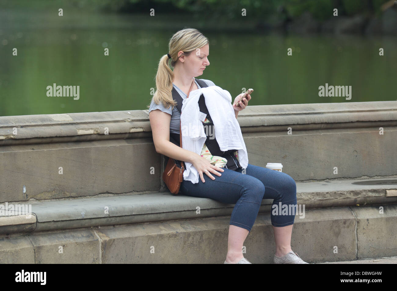 New mom with baby on phone Stock Photo