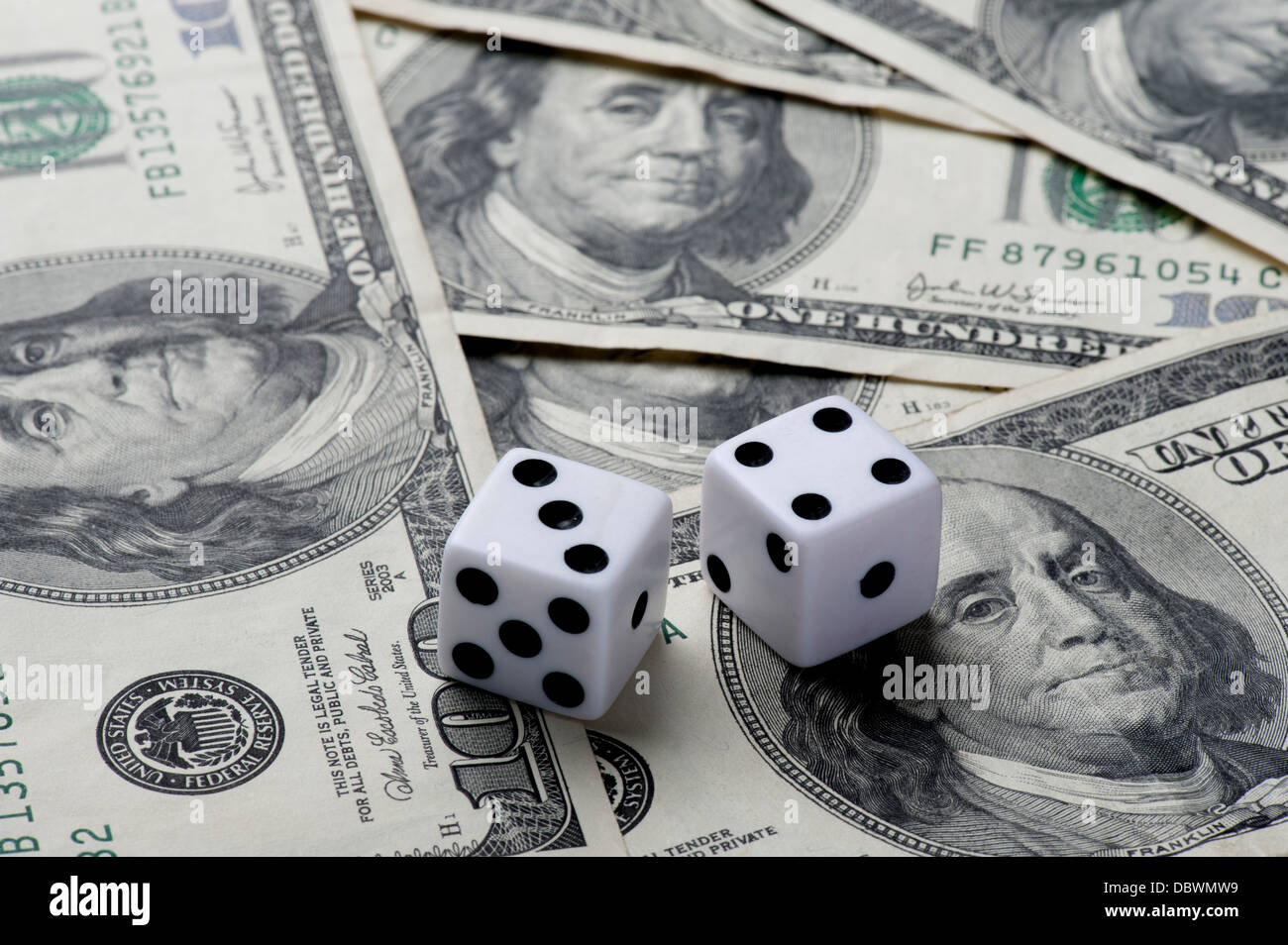 pair of dice on $100 bills concept gambling - Stock Image