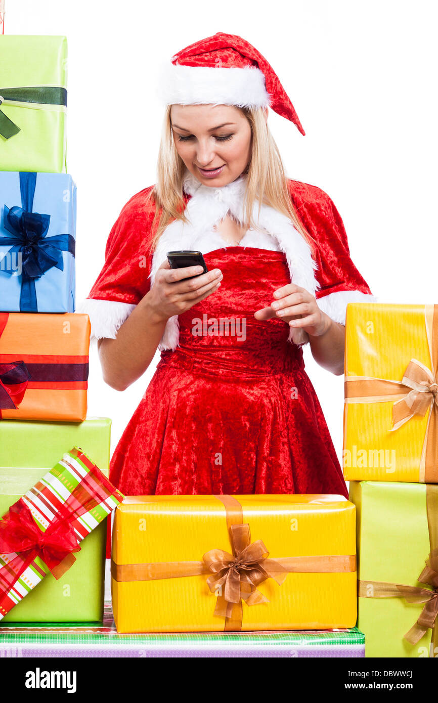 Christmas Woman texting message with phone surrounded by presents, isolated on white background. - Stock Image