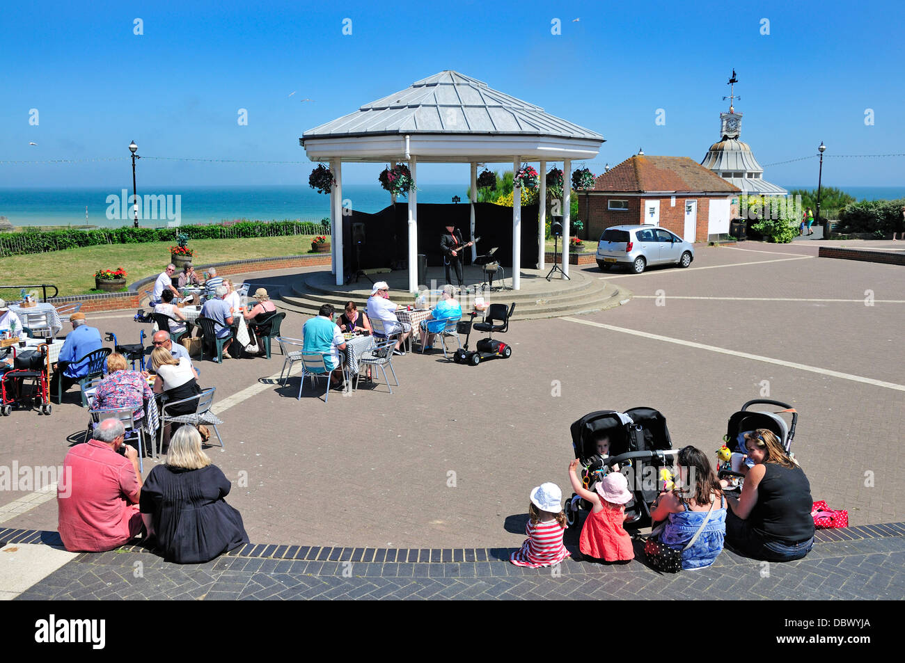 Broadstairs, Kent, England, UK. People listening to a musician at the bandstand - Stock Image