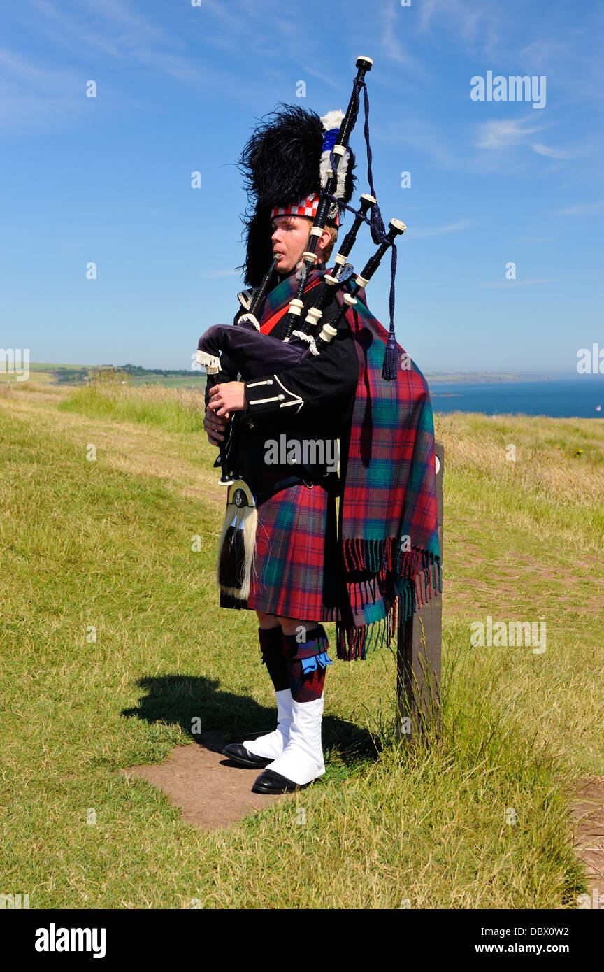 Piper in full highland dress at Dunnottar Castle near Stonehaven, Aberdeenshire, Scotland - Stock Image