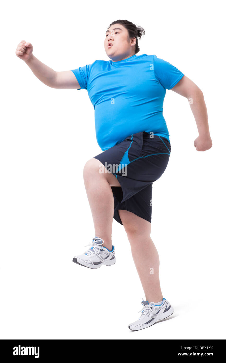 Overweight man running with difficulty - Stock Image