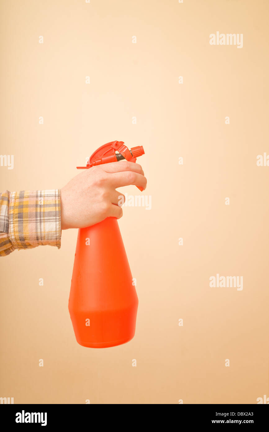 Water atomizer in female hands, plastic bottle for water spraying. - Stock Image