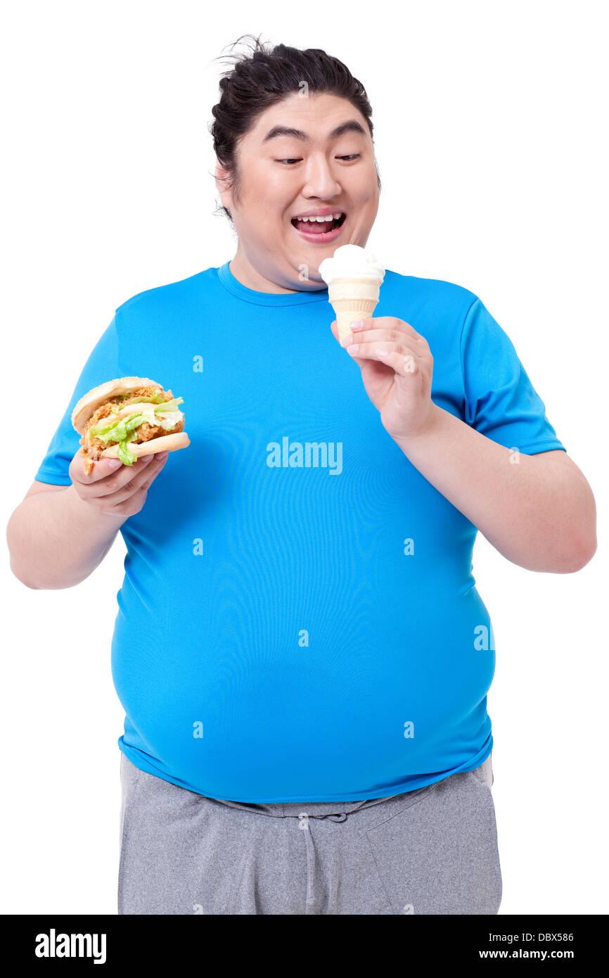 Greedy fat man eating burger and ice cream Stock Photo ...