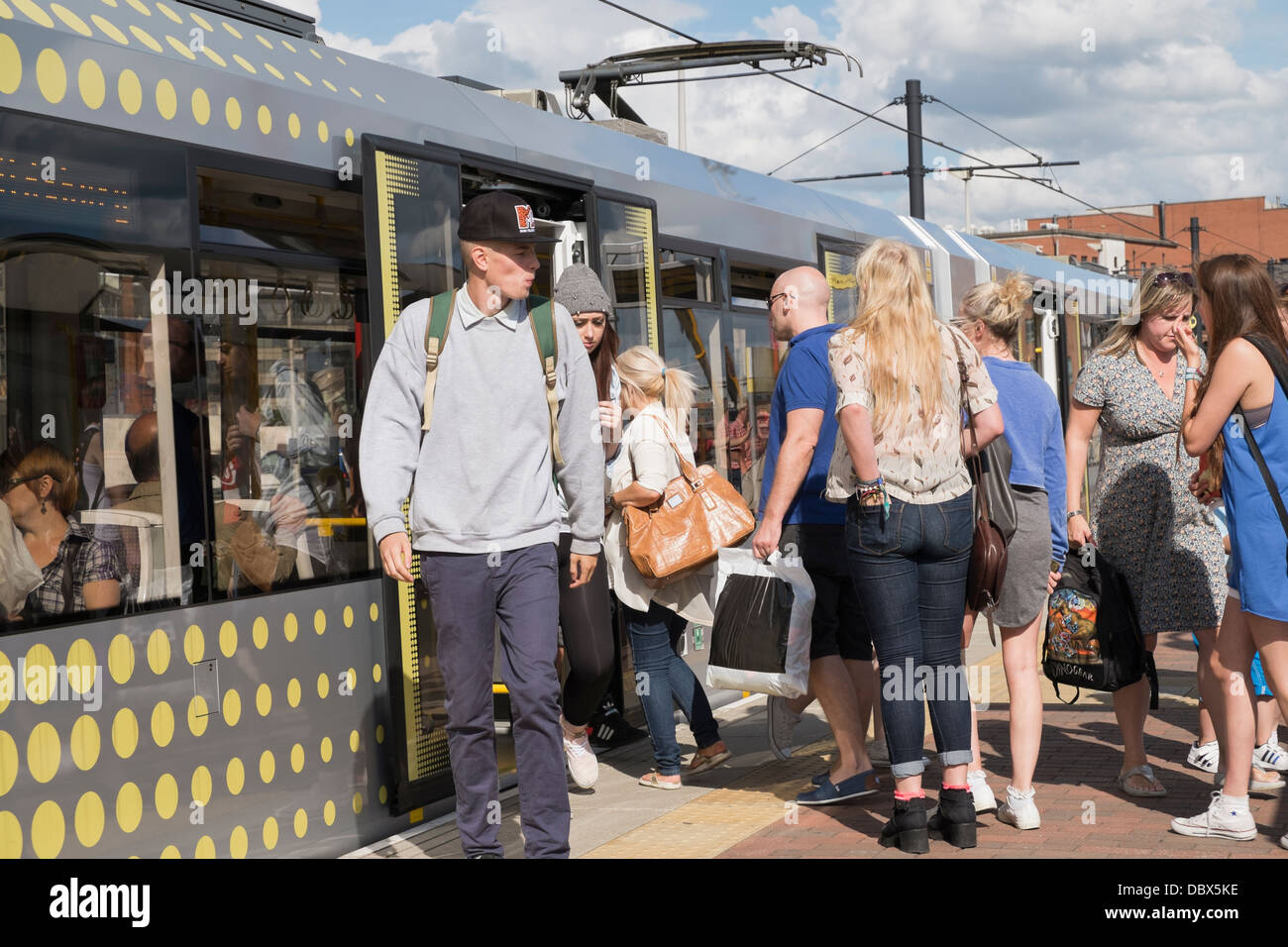 Everyday scene of passengers on crowded platform with people boarding a Metrolink tram at Deansgate-Castlefield - Stock Image