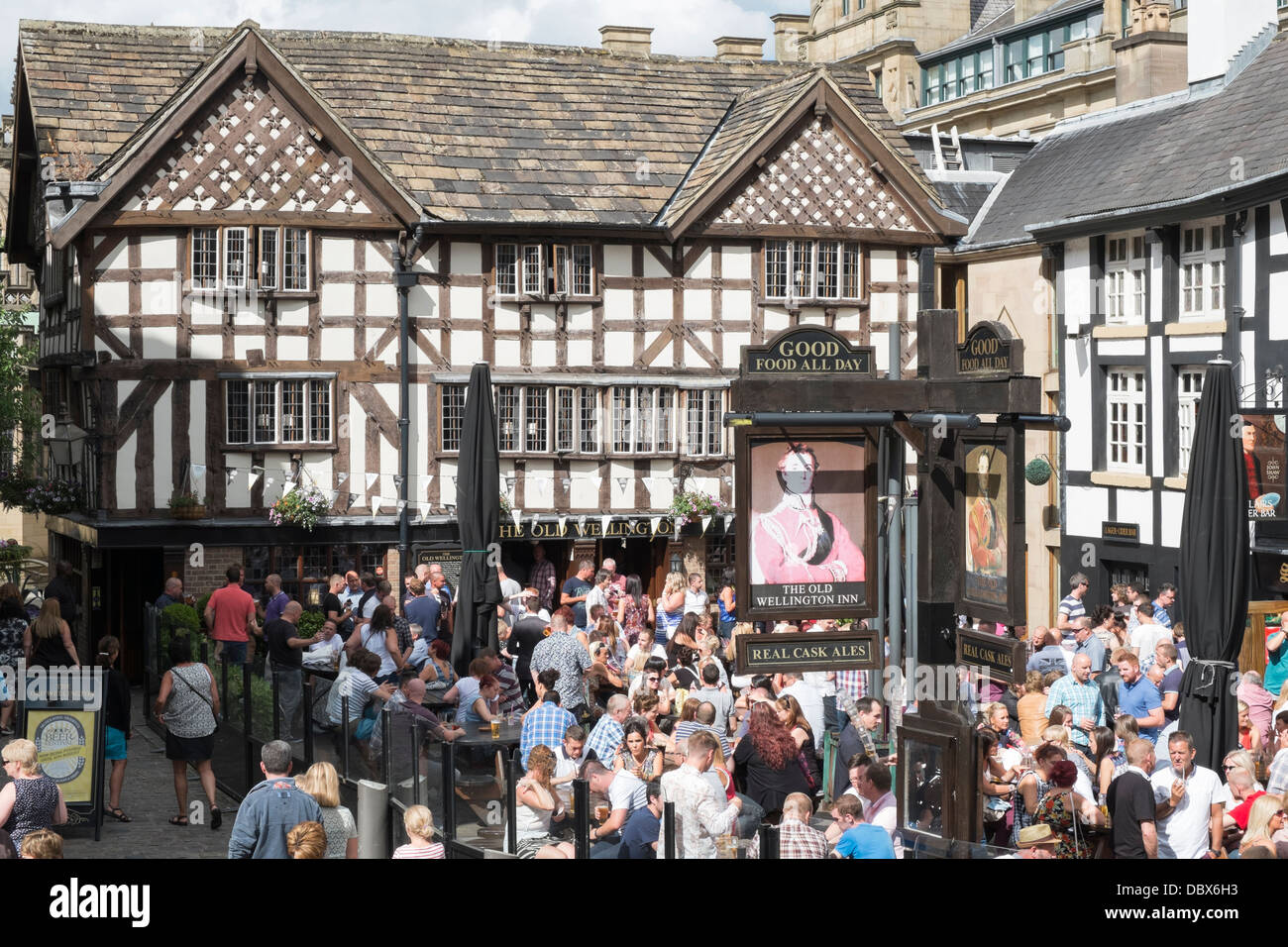 Crowds of people drinking outside 16th century timbered The Old Wellington Inn 1552 in summer in old Shambles Square - Stock Image