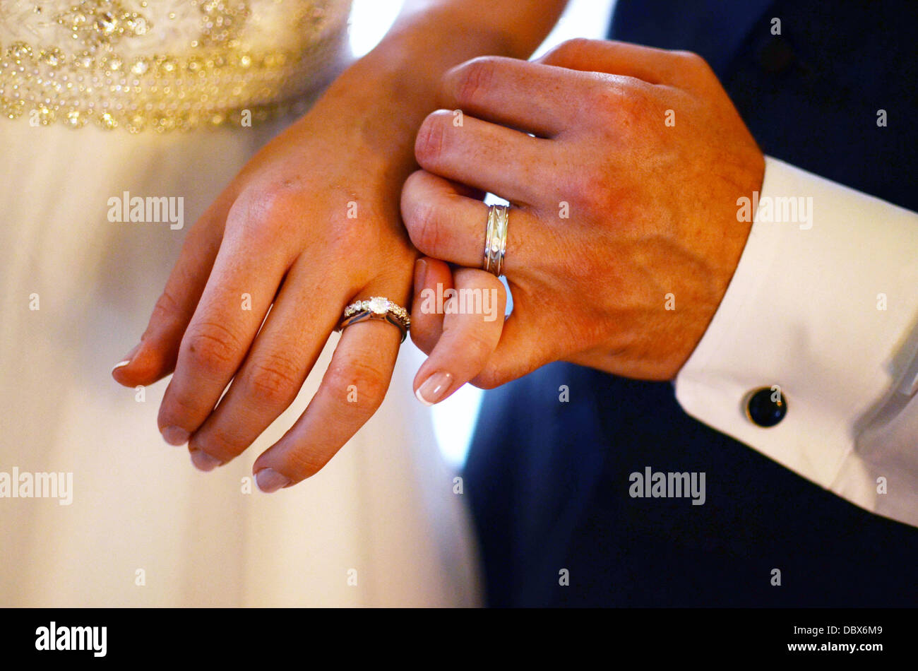 Newlywed bride and groom pinky promise after exchanging rings - Stock Image