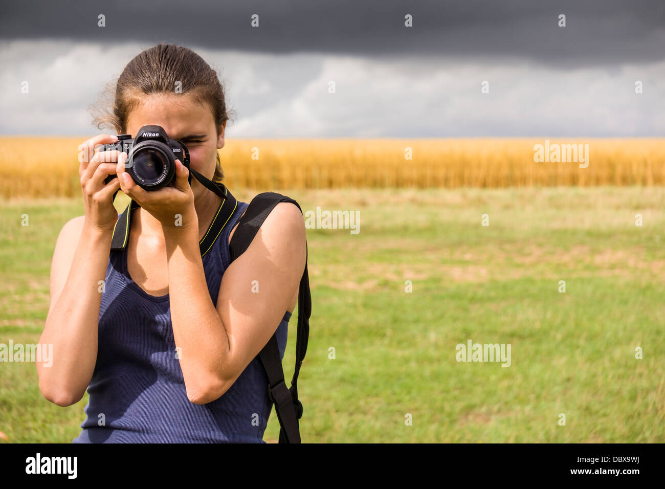 A young girl takes a photograph using a DSLR. - Stock Image