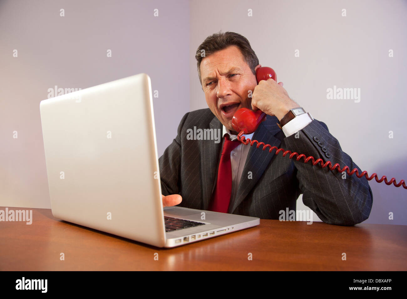 Angry man wearing a suit, shouting down a red telephone while sitting in front of a laptop on a desk. Stock Photo
