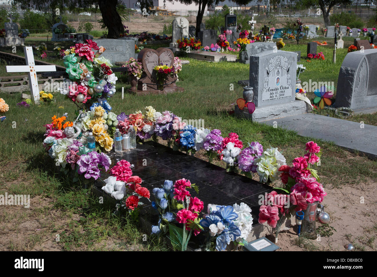 Mcallen Texas Artificial Flowers And Bottled Water On A Grave In