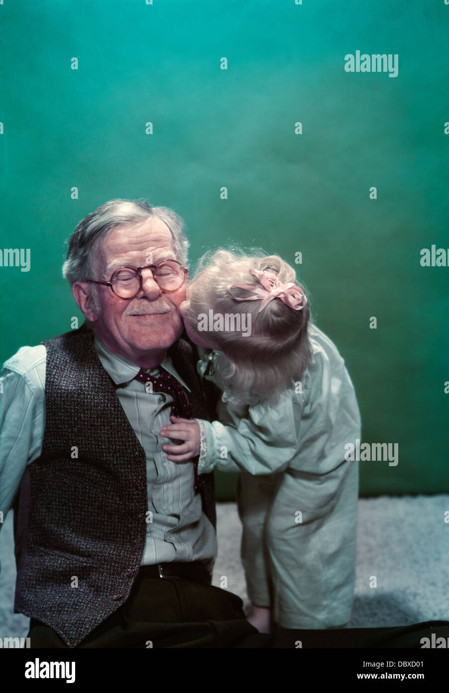 1940s 1950s GRANDDAUGHTER KISSING SMILING GRANDFATHER GOODNIGHT ON CHEEK - Stock Image