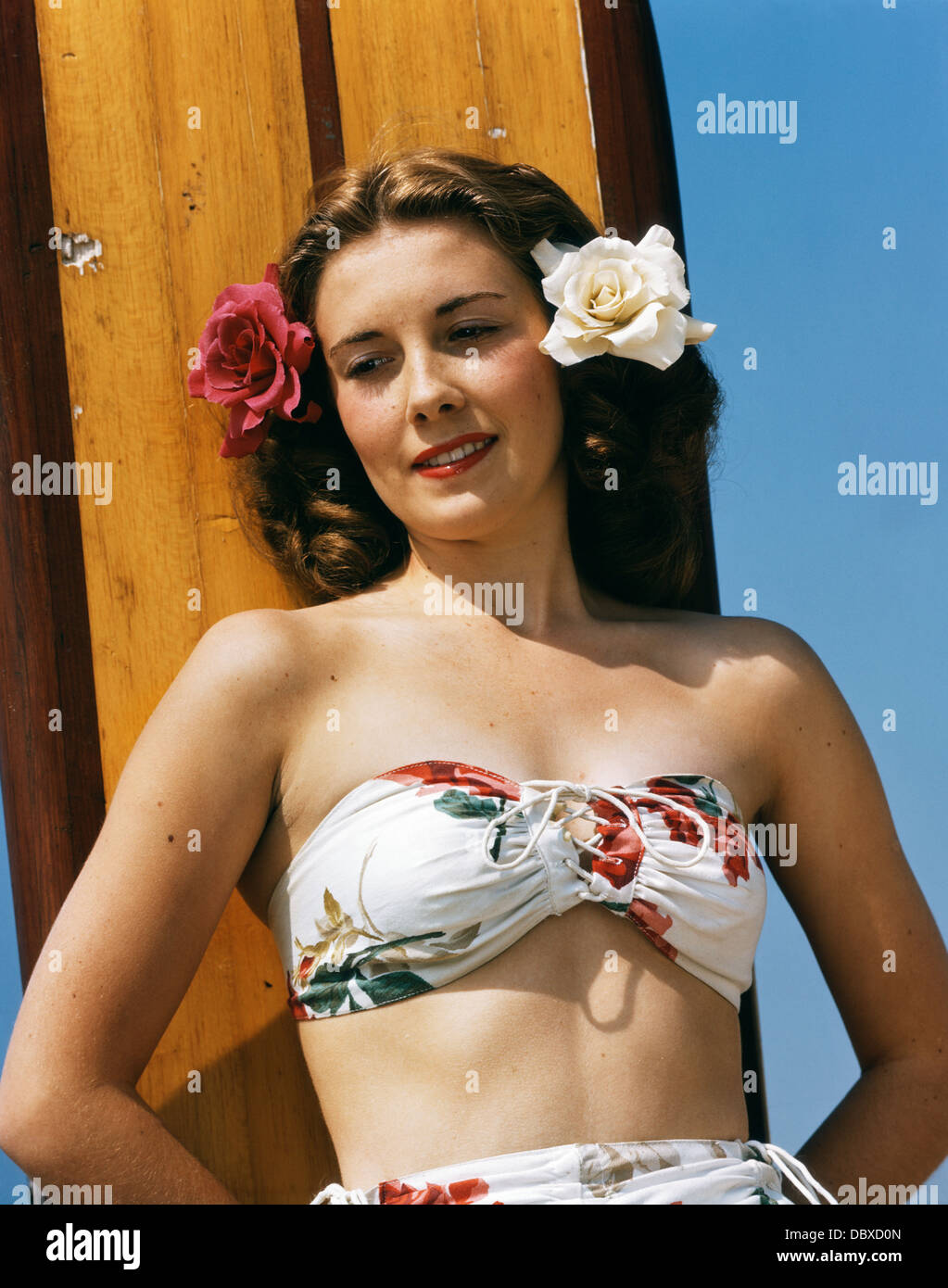1940s 1950s PORTRAIT WOMAN WEARING FLORAL PRINT BIKINI BATHING SUIT AND ROSES IN HAIR LEANING AGAINST SURFBOARD - Stock Image