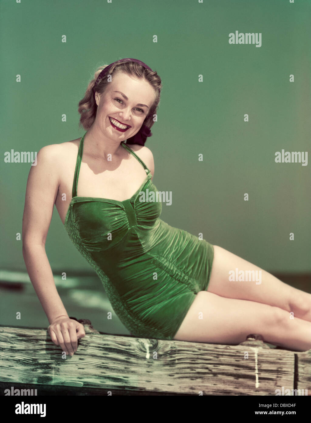 1940s PORTRAIT SMILING WOMAN WEARING GREEN VELVET BATHING SUIT SITTING POSING ON DIVING BOARD - Stock Image