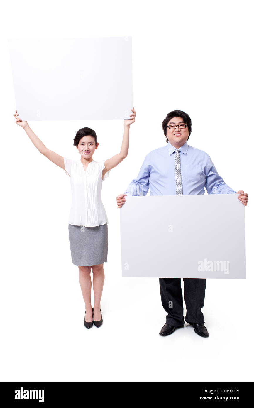Cheerful business partner holding whiteboard aloft - Stock Image