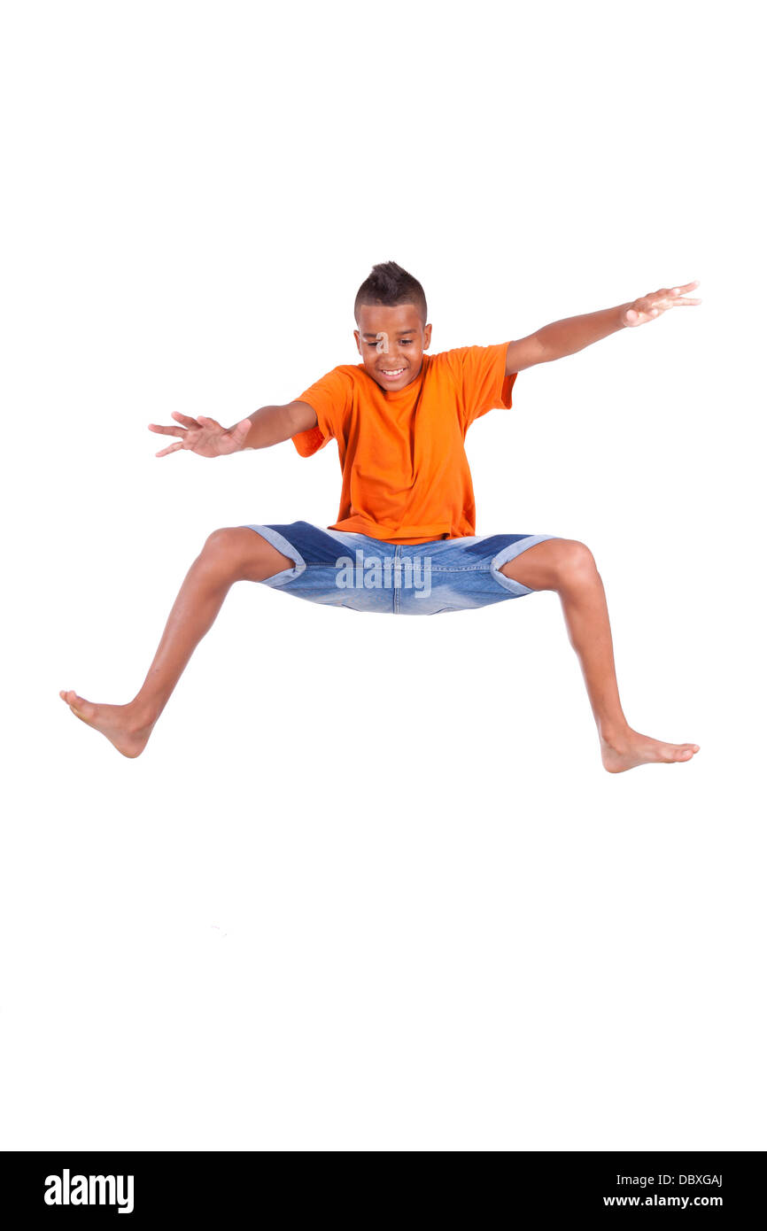 Portrait of a cute teenage black boy jumping over white background - African people - Stock Image