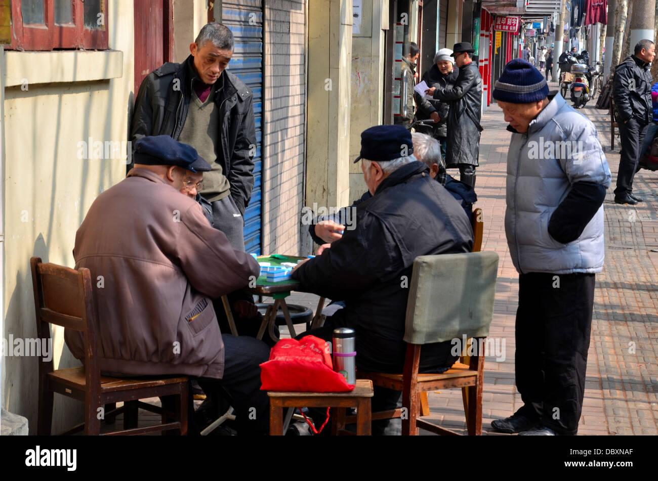 Street scene with mahjong game Shanghai, China - Stock Image