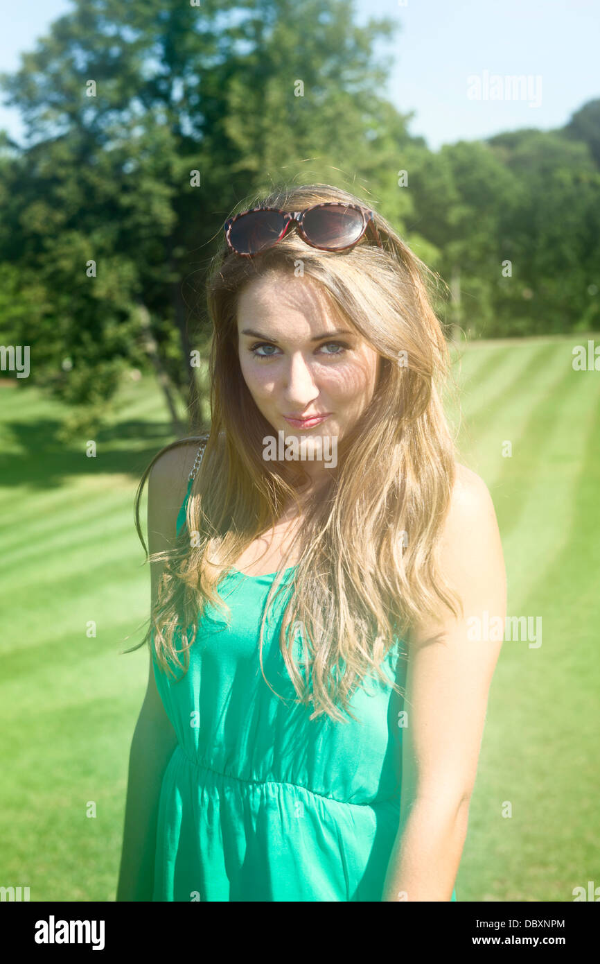 Young woman outside at a park, smiling with sunglasses on her head and wearing a green dress. - Stock Image