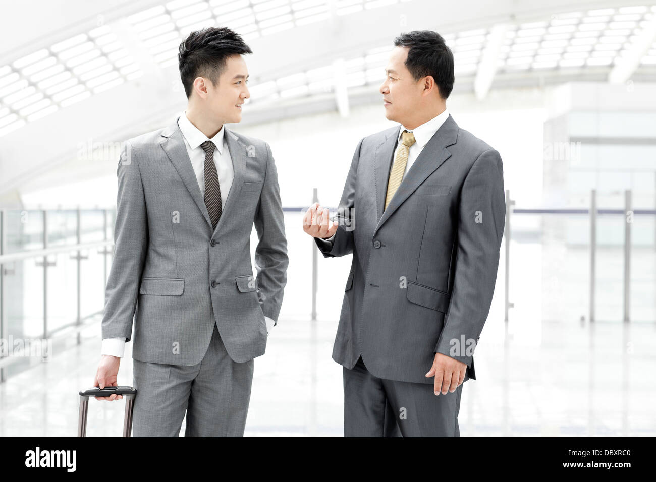 Business associates having conversation in airport lobby - Stock Image