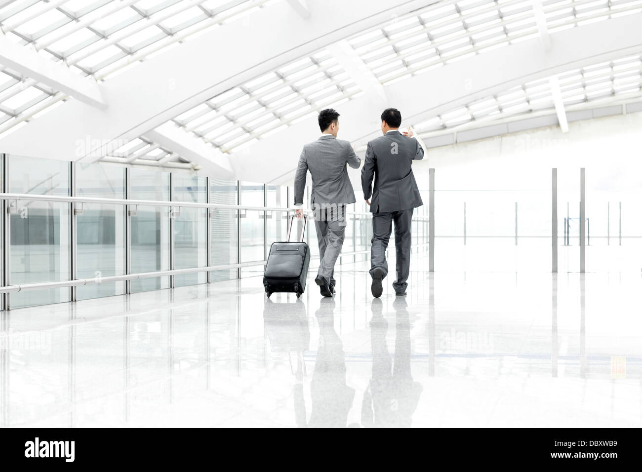 Business associates walking and talking in airport lobby - Stock Image