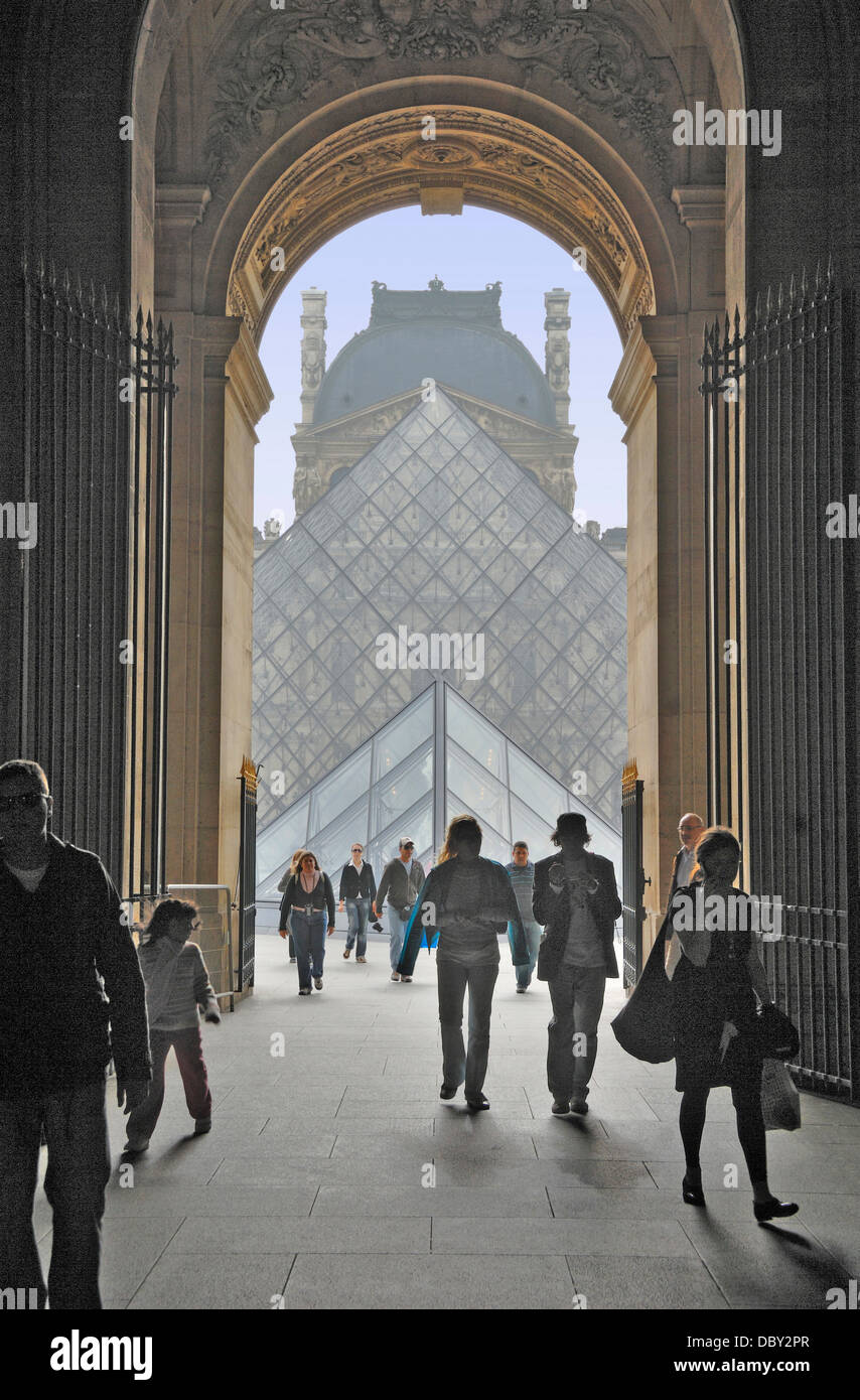 Visitors approaching and departing through an Archway at The Louvre Museum in Paris, France.  Behind is the glass Stock Photo
