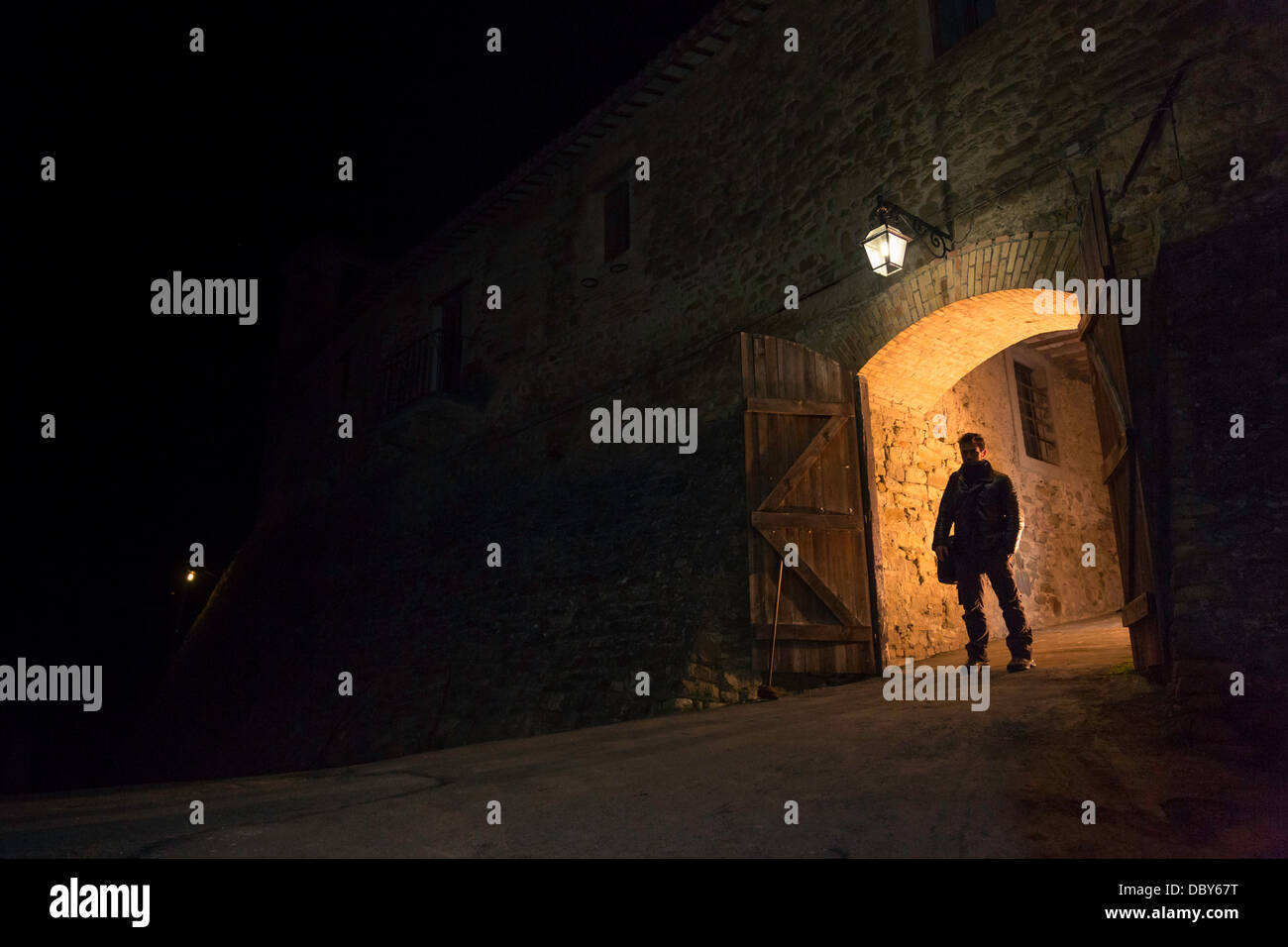 Man standing outside the gate of the medieval city - Stock Image
