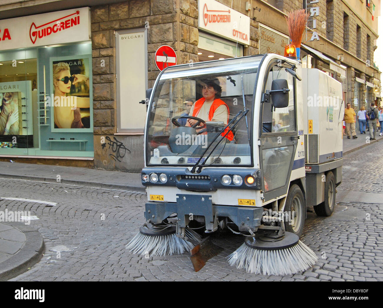 A woman cleaner on a cobblestone street in Florence, Italy Stock Photo