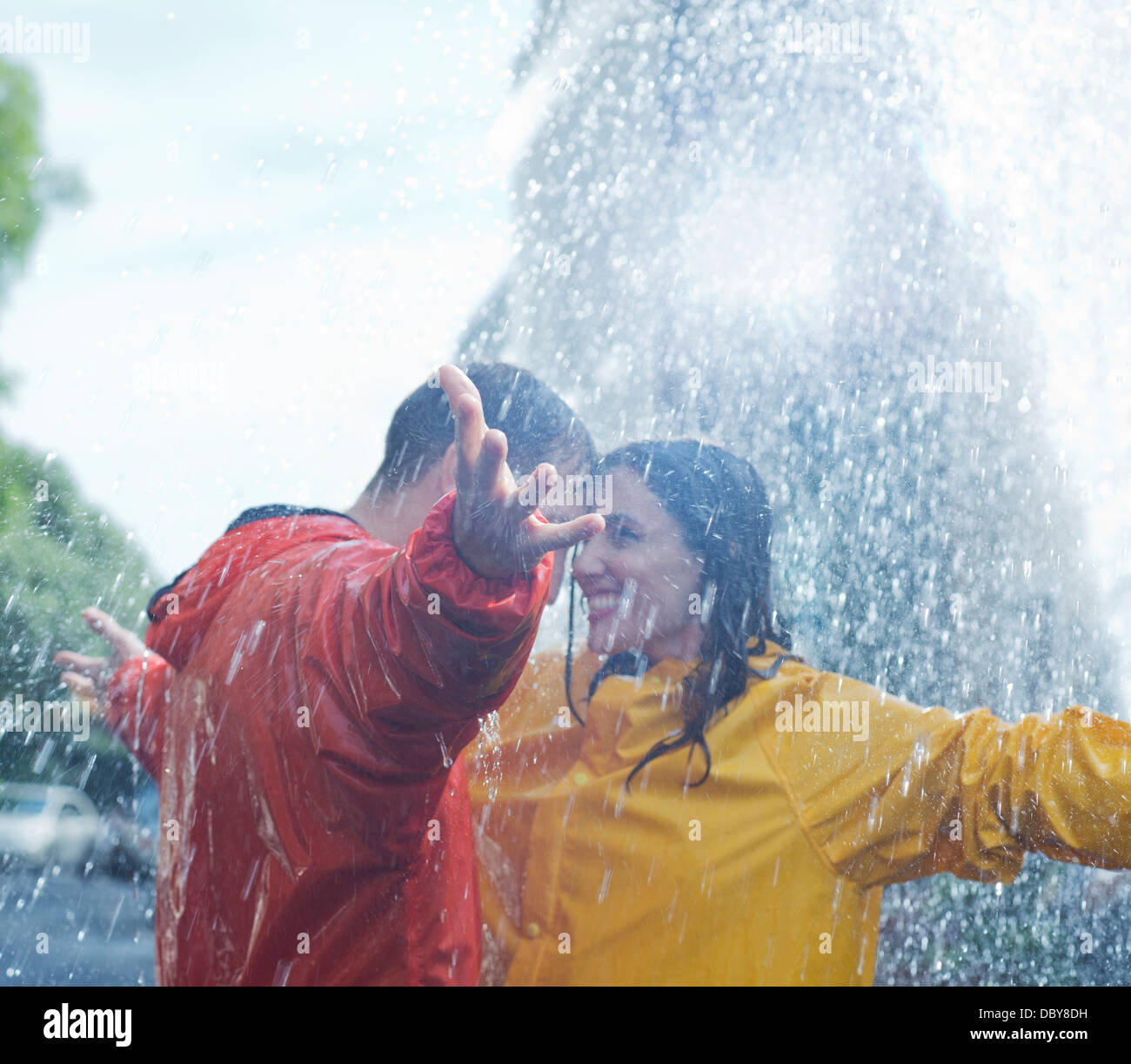 Happy couple dancing in rain - Stock Image