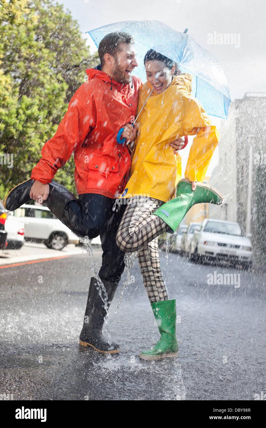 Happy couple in wellingtons splashing in rainy street - Stock Image