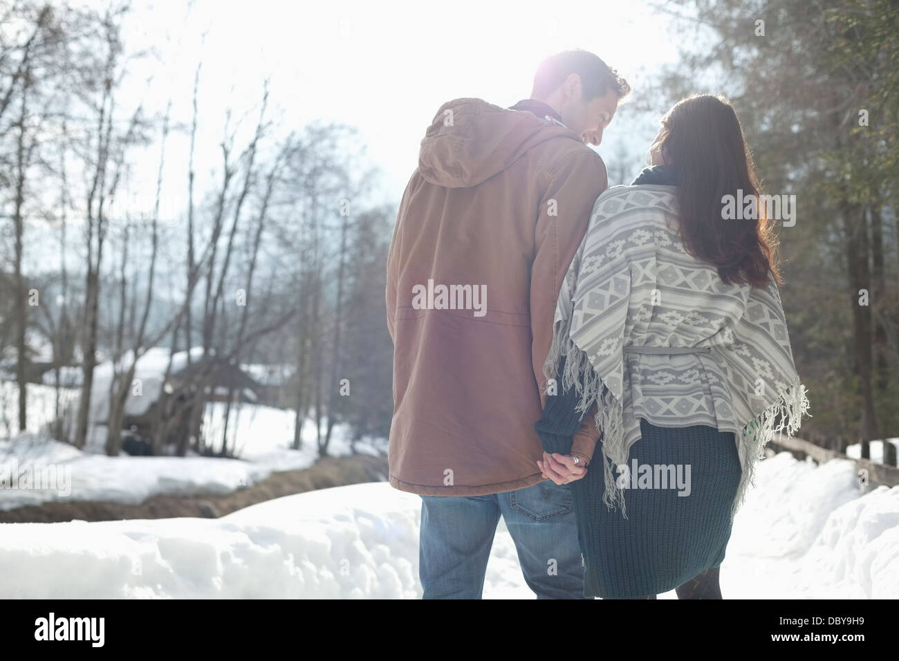 Couple holding hands and walking in snowy lane - Stock Image
