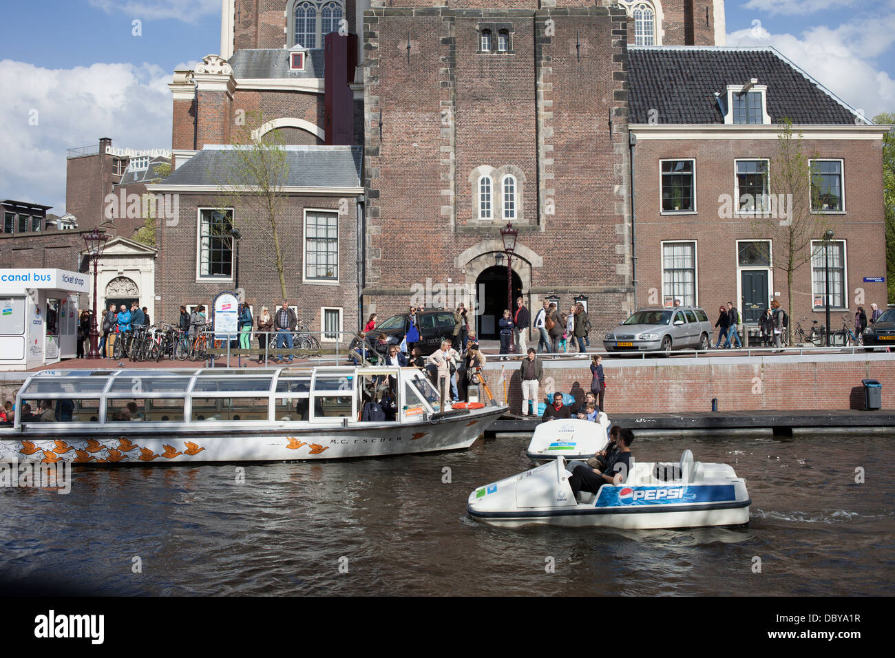 Pedal and passenger boats on Prinsengracht canal waterfront in front of Westerkerk in Amsterdam, Netherlands. - Stock Image