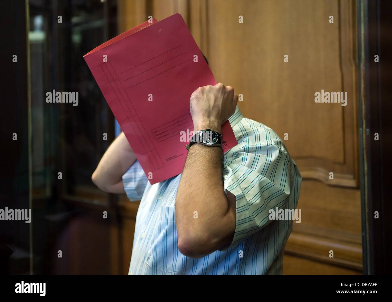 Accused Mehmet Oe. hides his face behind a folder at the criminal court Moabit in Berlin, Germany, 06 August 2013. - Stock Image