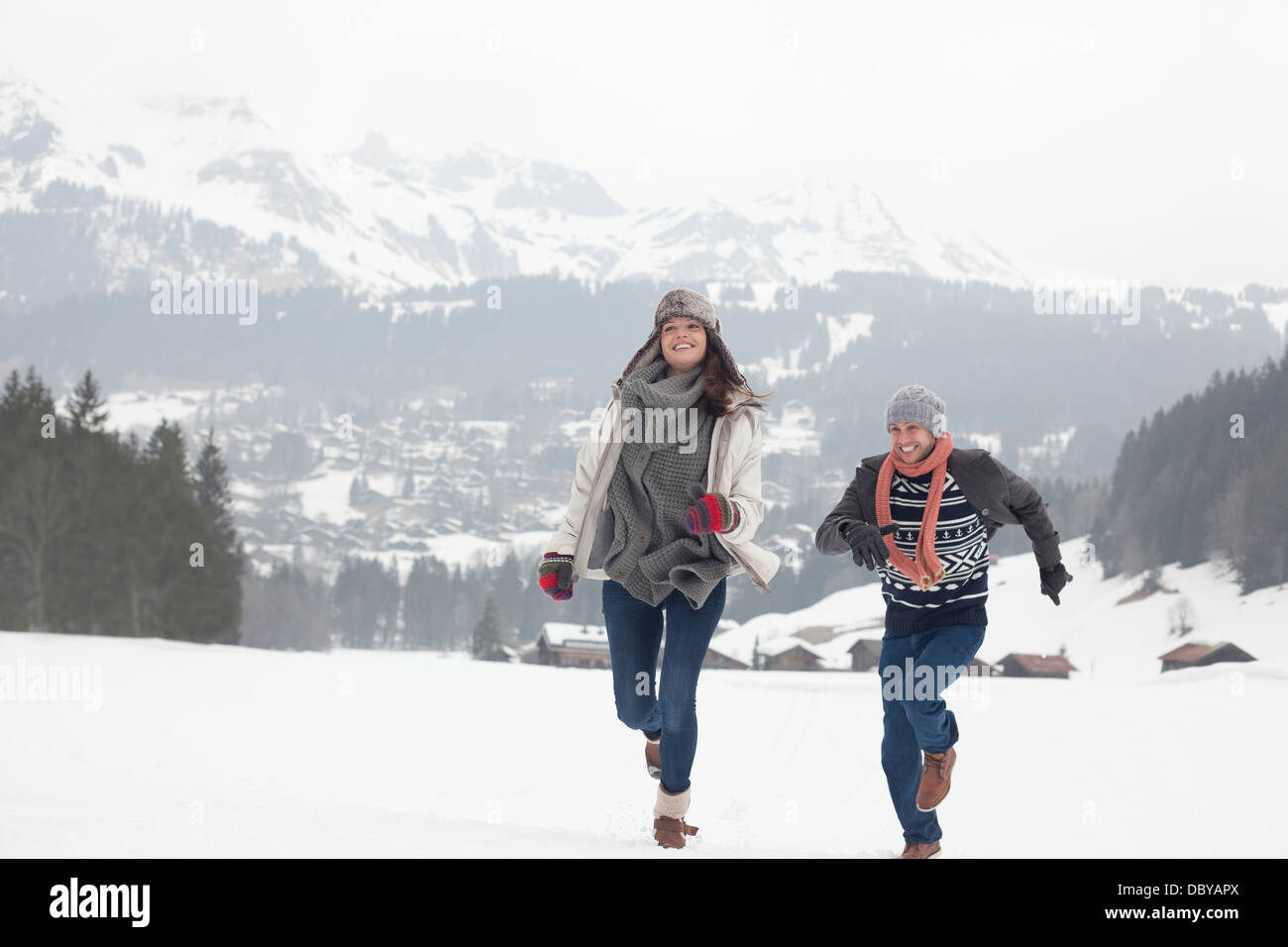 Happy couple running in snowy field - Stock Image