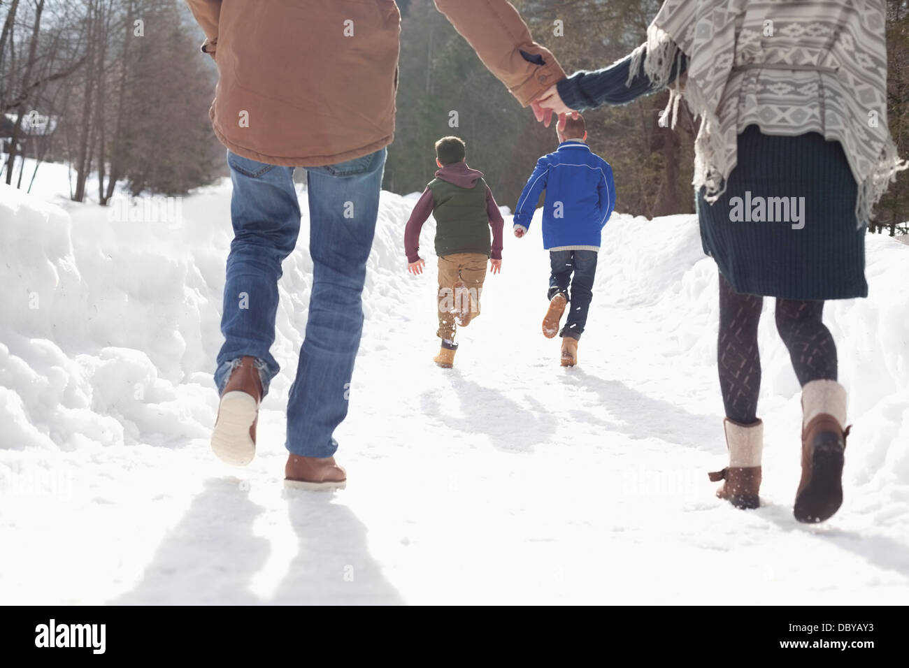 Happy couple holding hands and watching boys run in snowy lane - Stock Image