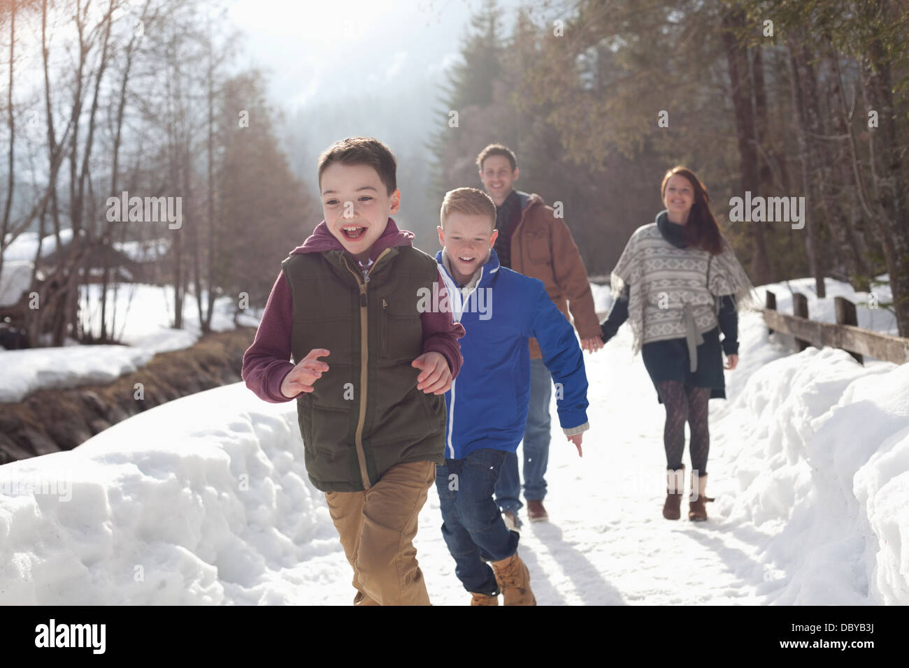 Happy family running in snowy lane - Stock Image