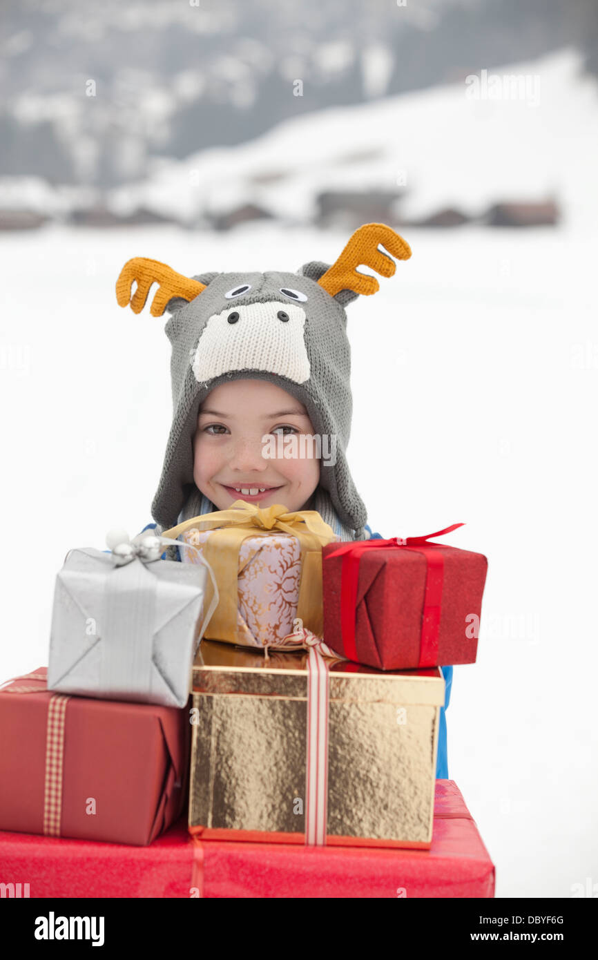 Portrait of smiling boy wearing reindeer hat and carrying stack of Christmas gifts in snow - Stock Image