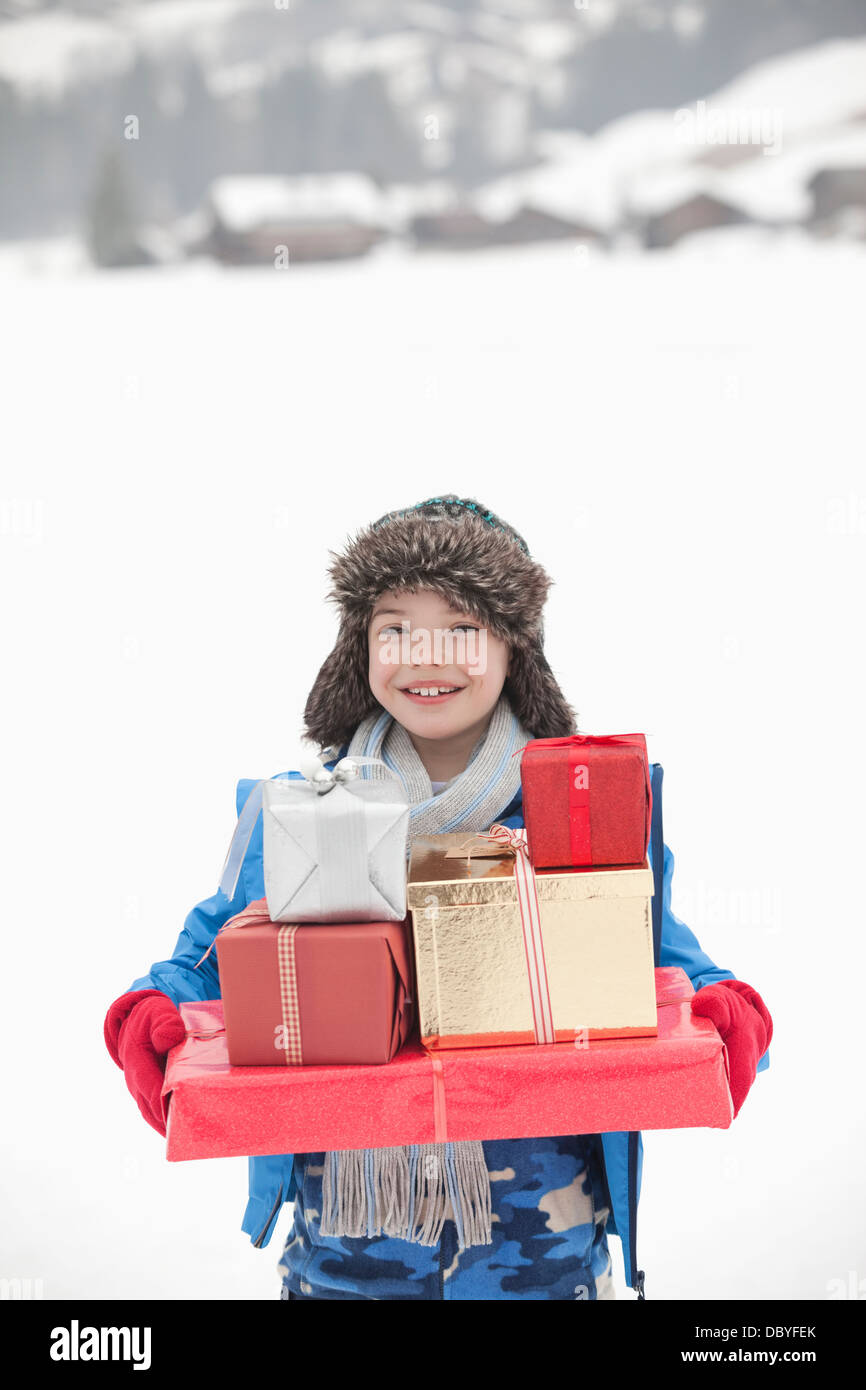 Portrait of smiling boy carrying stack of Christmas gifts in snow - Stock Image
