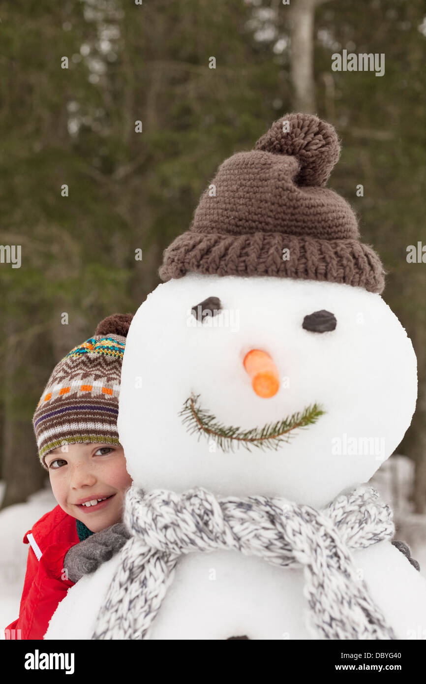 Portrait of smiling boy behind snowman with stocking-cap - Stock Image