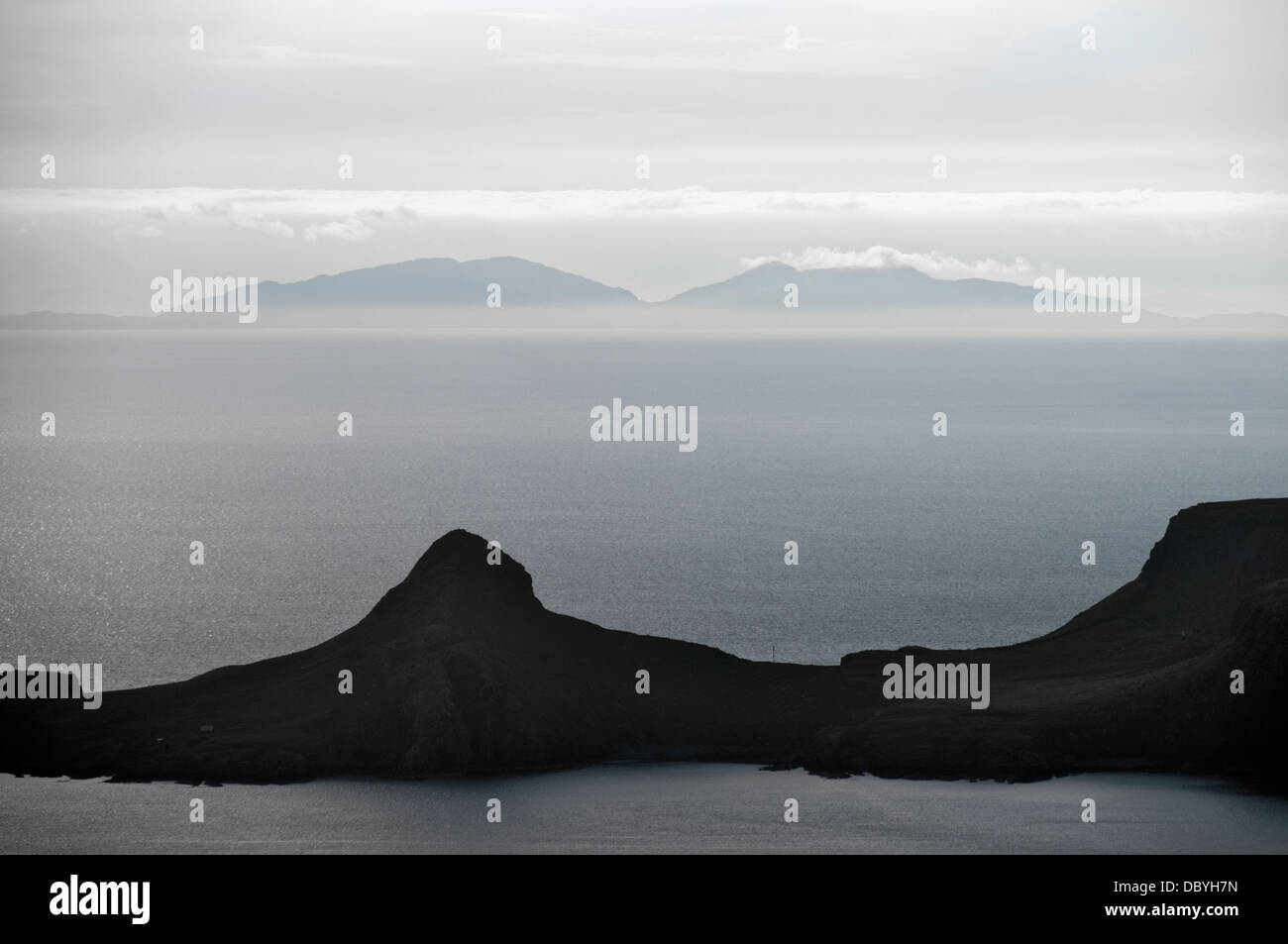 The Western Isles over the waters of the Minch with Neiss Point, Duirinish, on the Isle of Skye in the foreground. Stock Photo