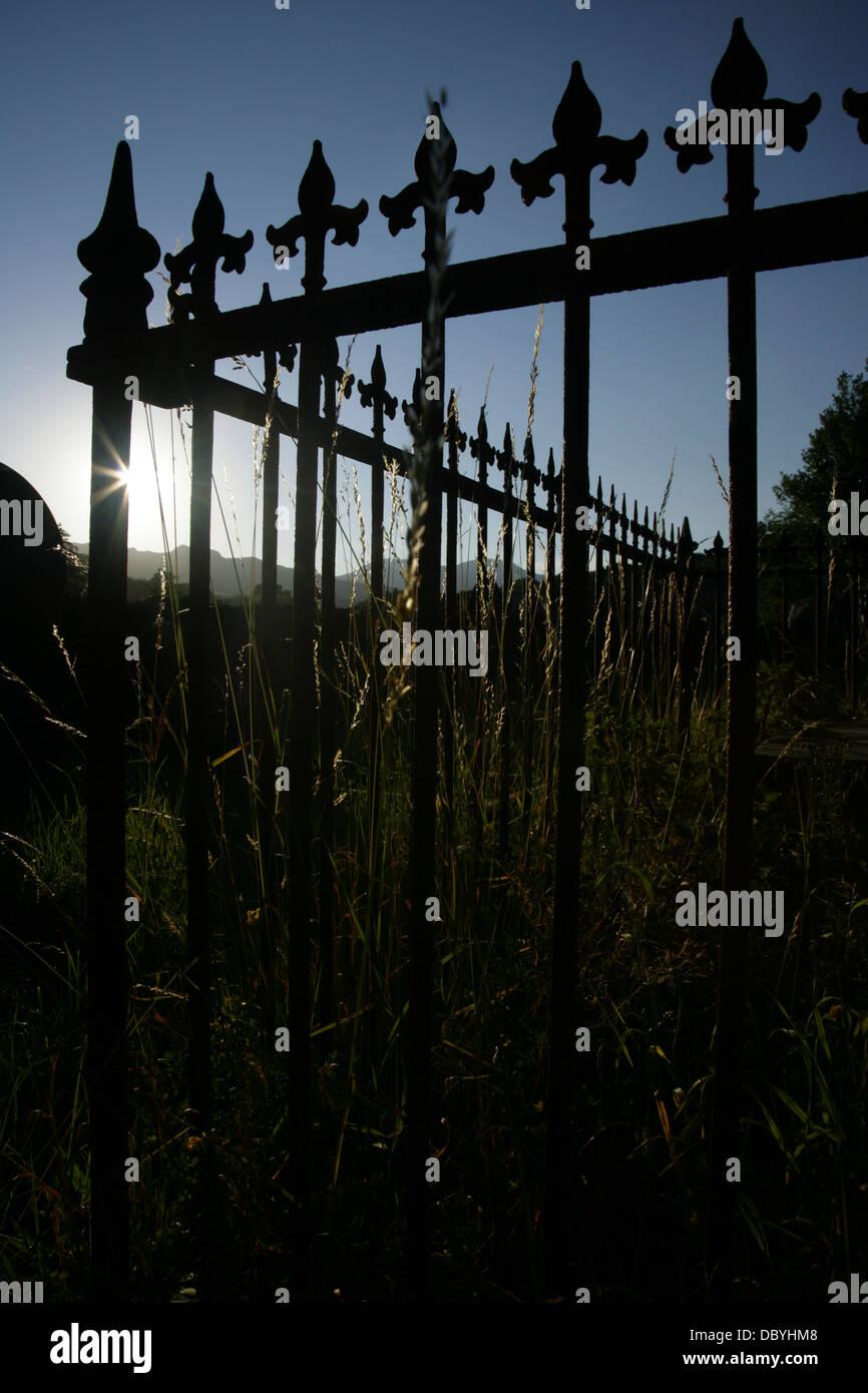 Ornate cast iron railings around old grave in St. Mary's churchyard, Beddgelert, Gwynedd, Snowdonia, Wales. - Stock Image