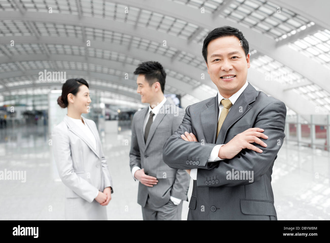 Confident business people in airport lobby Stock Photo