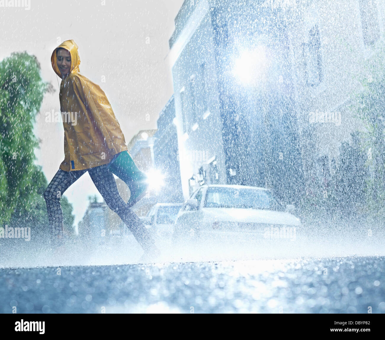 Woman walking barefoot on rainy street Stock Photo