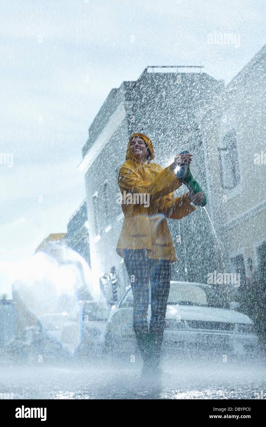 Happy woman walking barefoot in rain - Stock Image