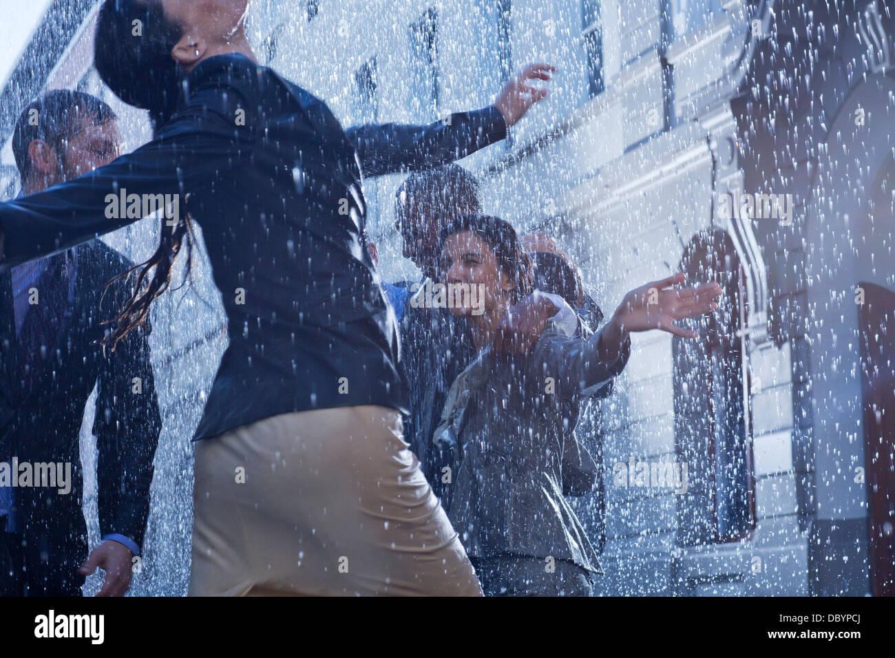 Business people dancing in rain - Stock Image